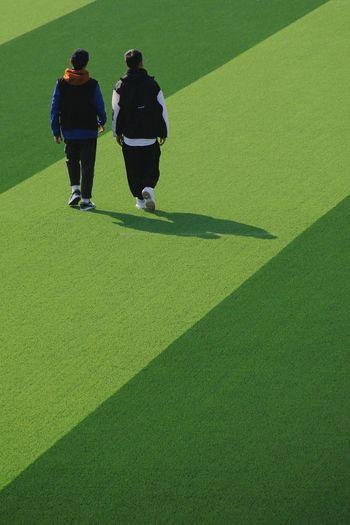 Rear view of two people walking on zebra crossing