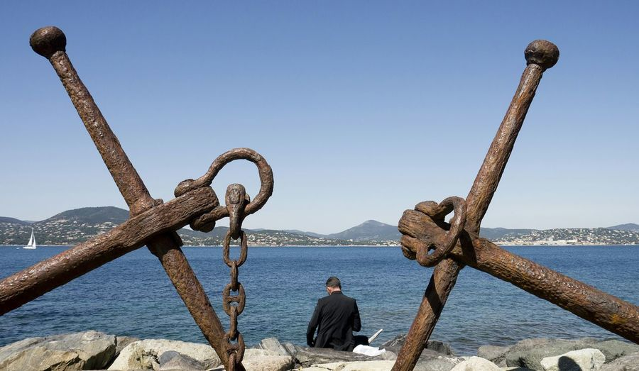 Symmetrical view of rusty anchors on rocky coast