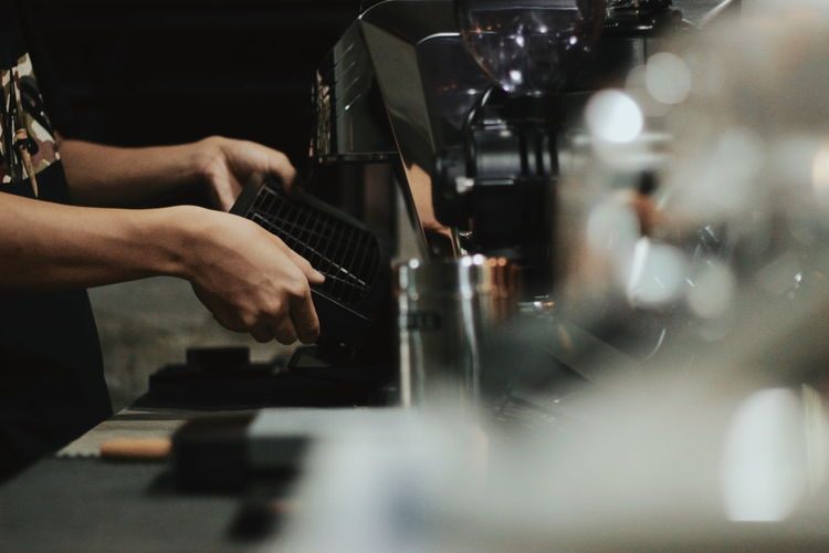 Cropped image of barista making coffee in cafe