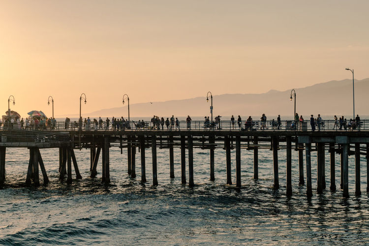 Beach Beauty In Nature Day Nature Outdoors Pier Real People Reflection Scenics Sea Silhouette Sky Sunset Tranquility Water Waterfront Wooden Post