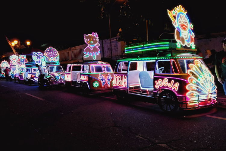 Illuminated carousel on road in city at night