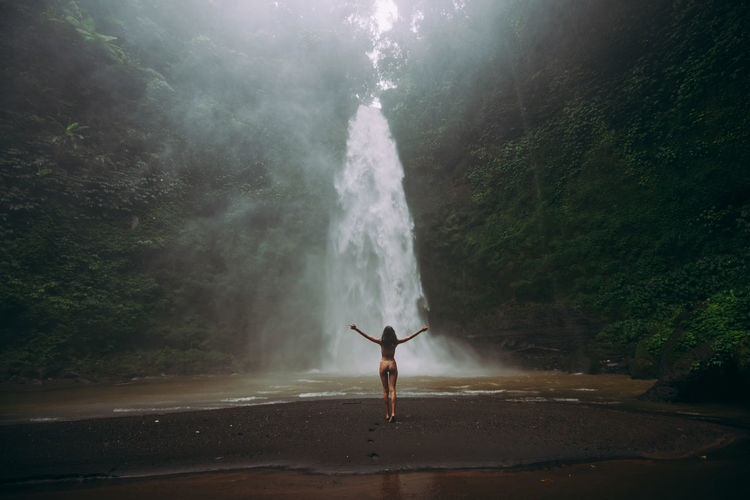 Young woman standing against waterfall