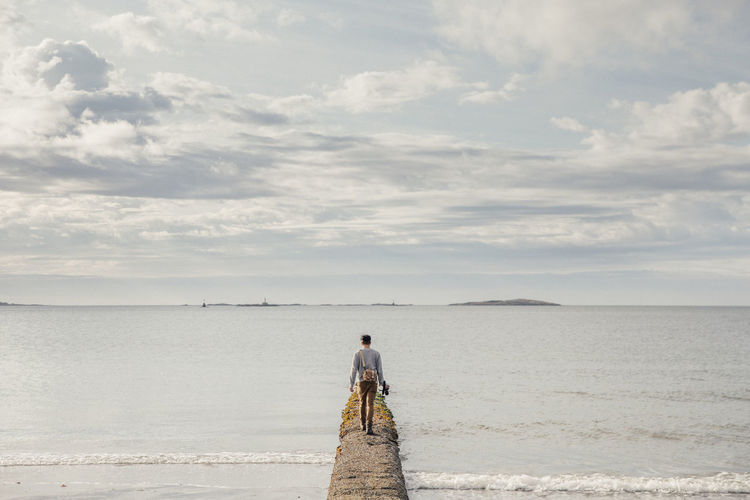 Rear View Of Man Walking On Pier In Sea Against Sky