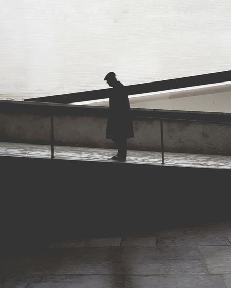 Silhouette woman standing by railing against sea