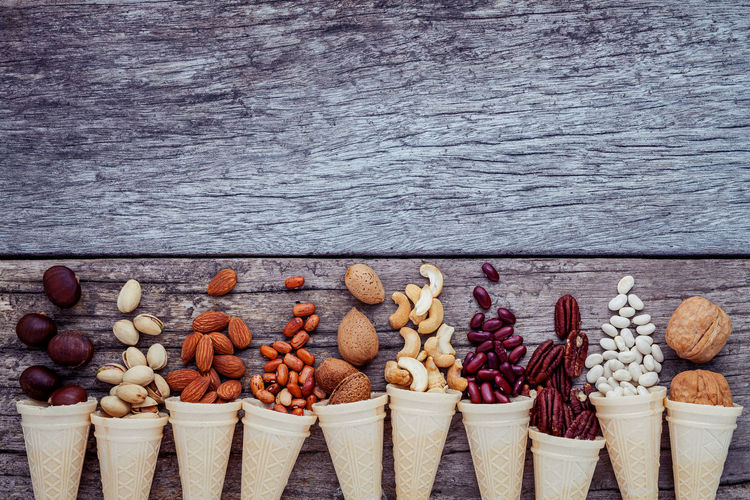 High angle view of ice cream cones with nuts on wooden table