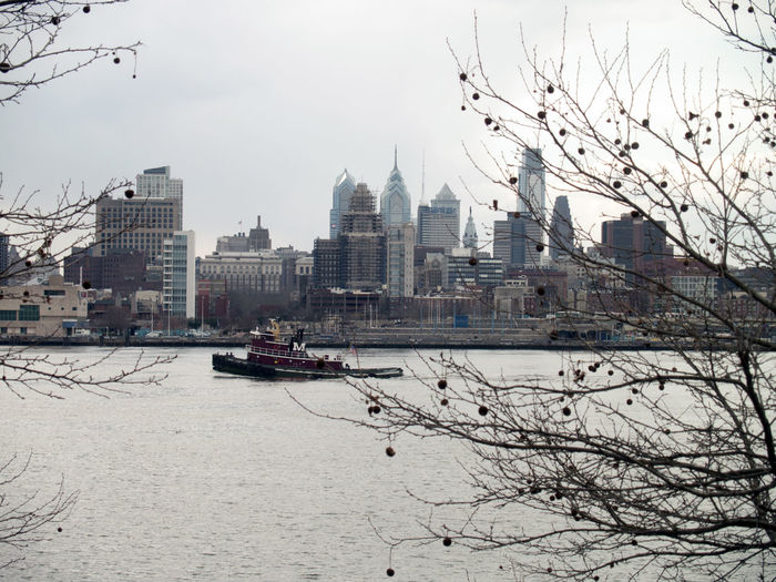 Ferry sailing in river by city skyline against clear sky