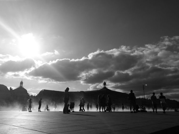 Silhouette people at town square against sky