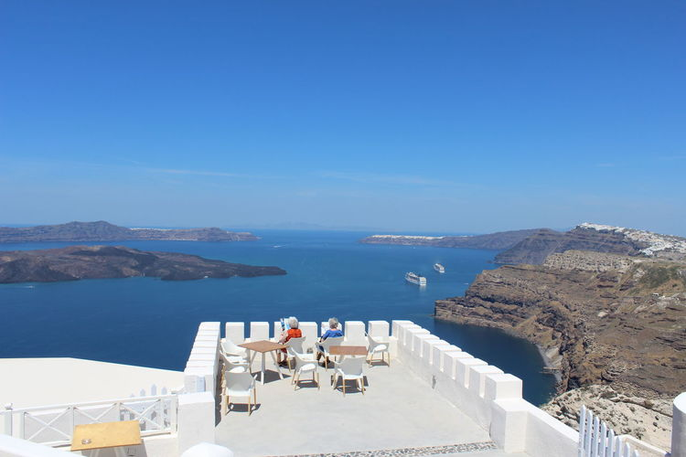 Rear View Of Senior Women Sitting On Terrace By Sea Against Sky At Santorini