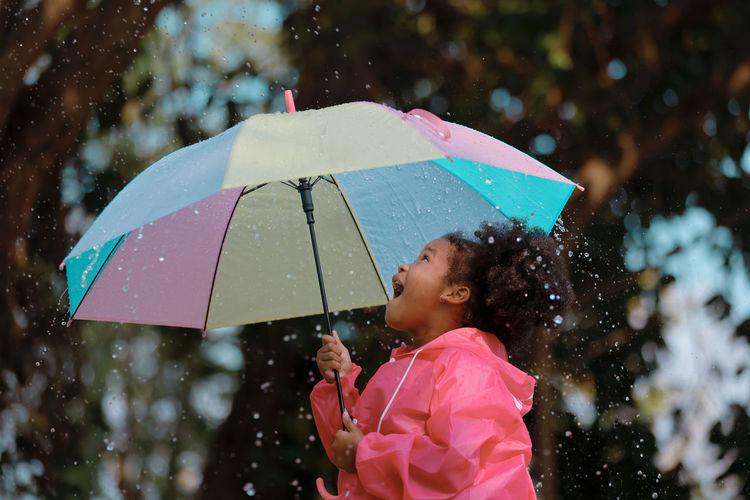 Woman holding wet umbrella during rainy season