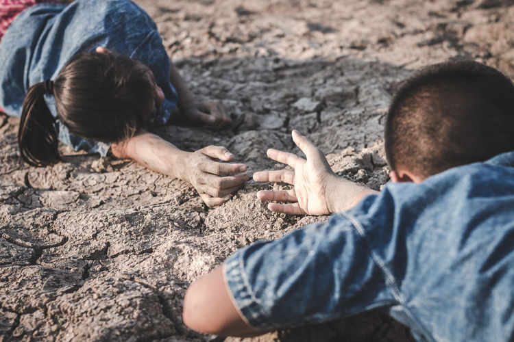 Siblings lying on cracked land