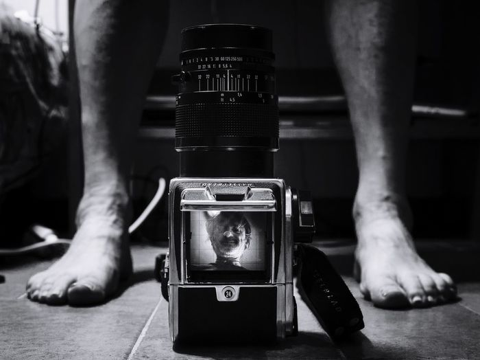 Low Section Of Man By Digital Camera On Floor At Home