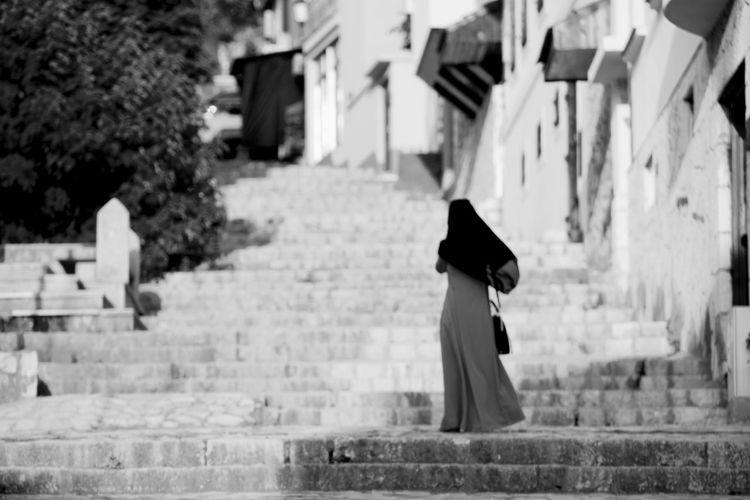 Side view of woman walking against buildings in city