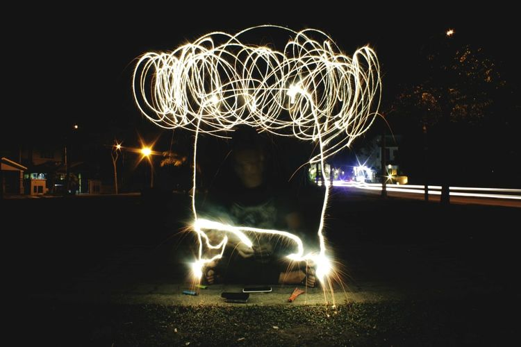Man with sparkler making light trails at night