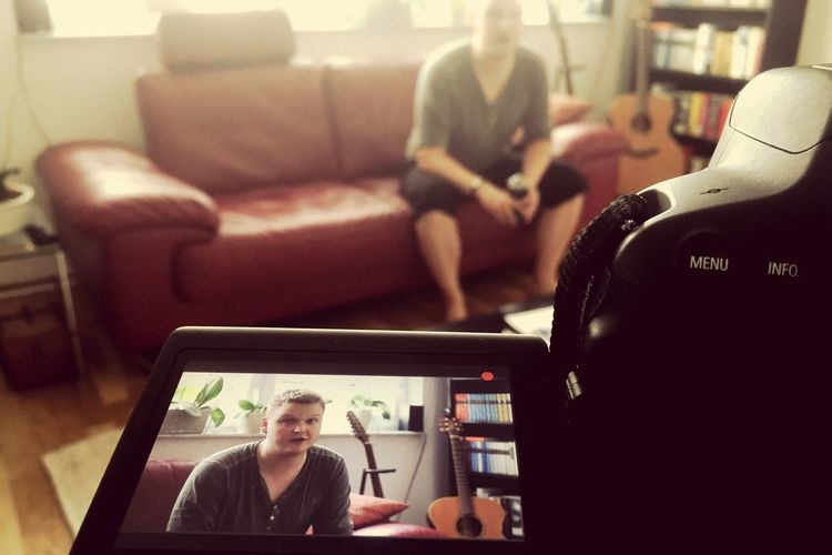 Close-up of camera filming man sitting on sofa at home