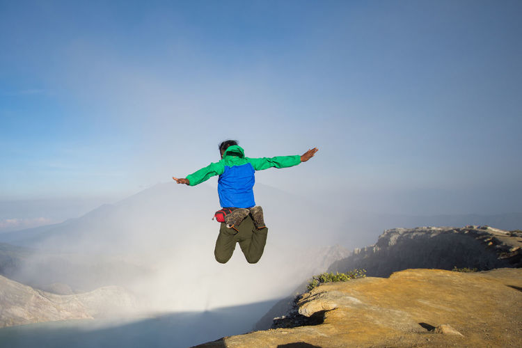 Man jumping in mountain against sky
