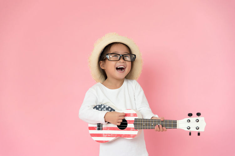 Girl wearing eyeglasses and hat while playing guitar against pink background