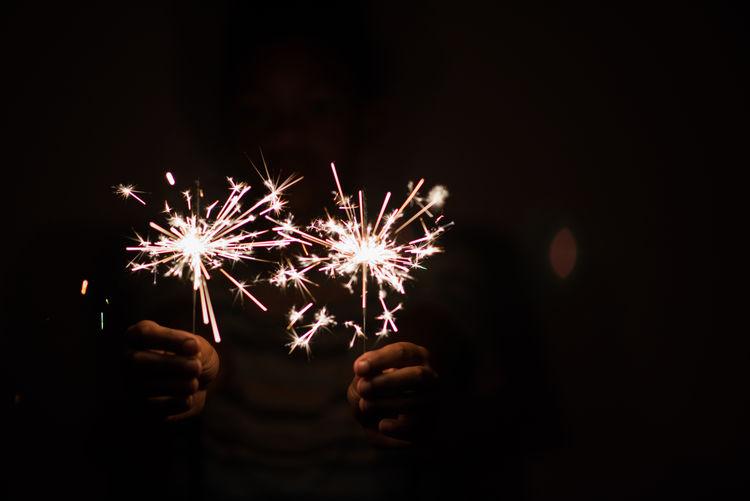 Cropped hands holding lit sparklers in darkroom