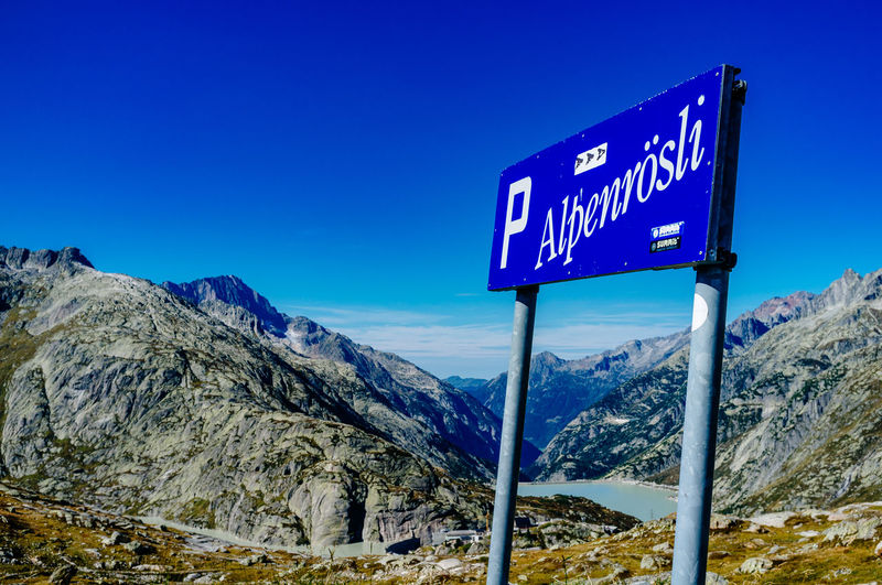 Road sign at mountain against blue sky