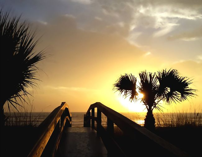 Footbridge leading towards beach against sky during sunset