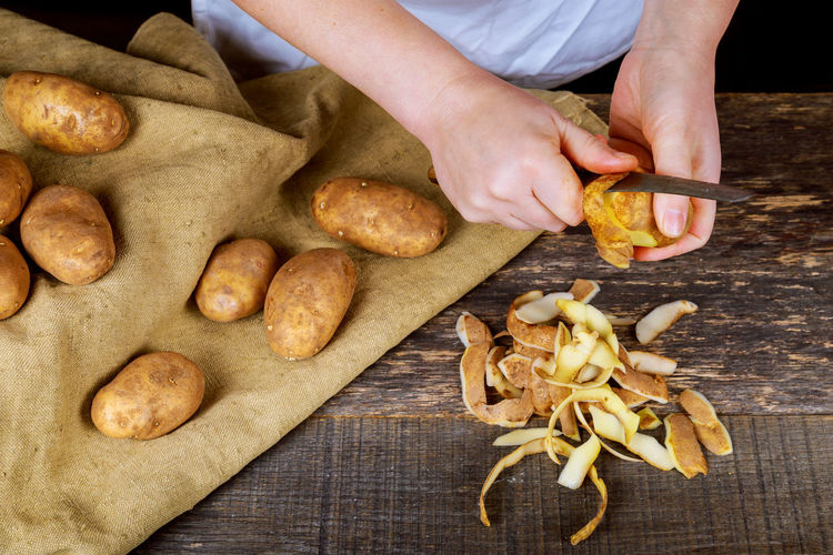 Midsection Of Man Peeling Potatoes On Wooden Table