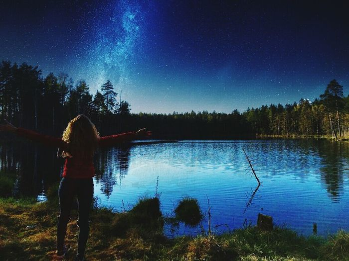 Rear view of woman standing by lake against sky at night