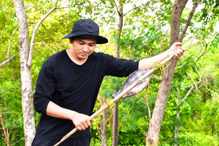 Man holding stick with fish while standing against trees in forest