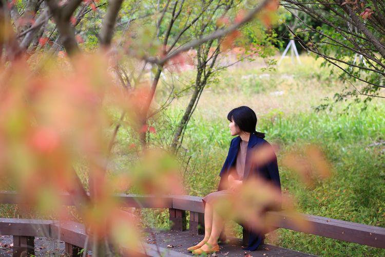 Woman sitting on boardwalk