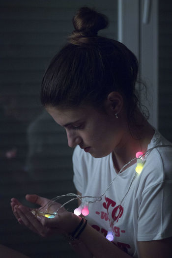 Side view of woman looking while holding illuminated lights