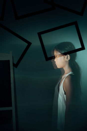 Double exposure of girl looking away while standing against wall at home