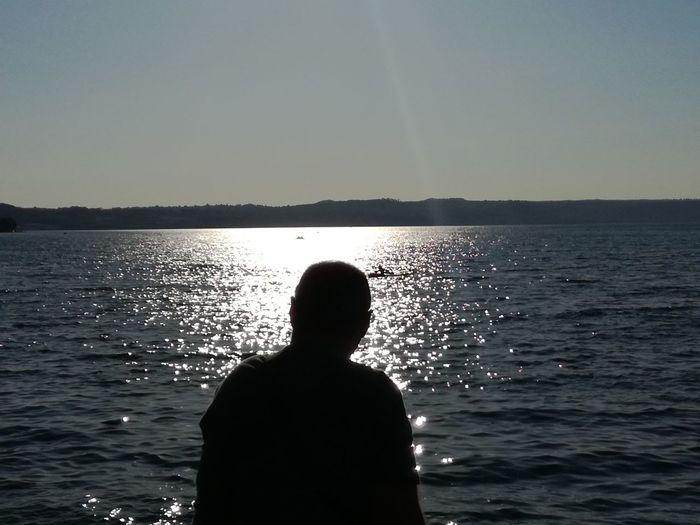 Silhouette man against sea against clear sky