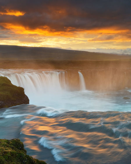 Scenic view of a waterfall in a wide sunset landscape, the colorful light reflected in the water, dark clouds above the scene - Location: Iceland, Goðafoss Iceland Travel Beauty In Nature Cascade Cloud - Sky Colorful Colorful Sky Idyllic Long Exposure Motion Nature No People Orange Color Outdoors River Scenics Sky Sunset Tranquil Scene Tranquility Travel Destinations Water Water Motions Waterfall Wide Area Network