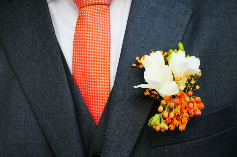 Midsection of groom with flowers in pocket
