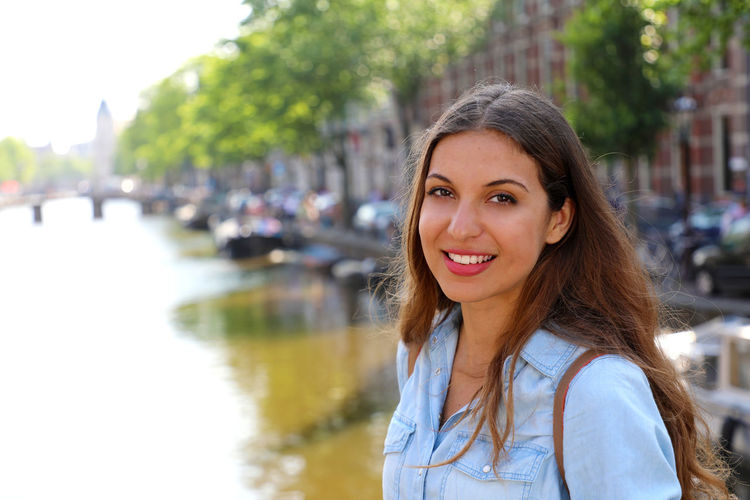 Portrait of young woman standing by canal in city