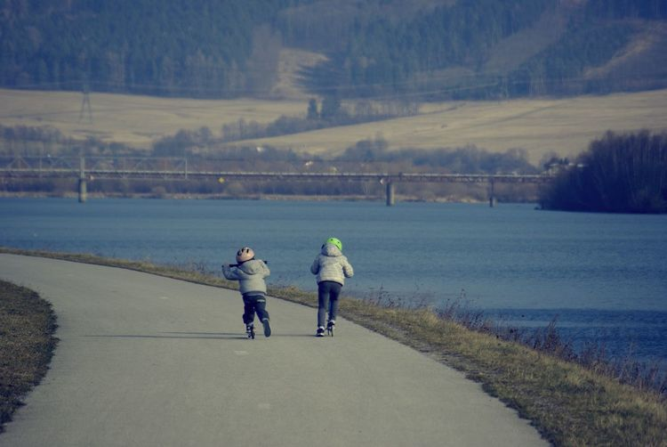 Rear View Of Sibling Roller Skating On Footbath By River