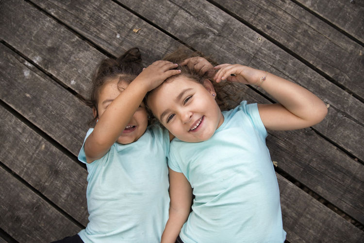 High angle portrait of cute sisters lying on deck