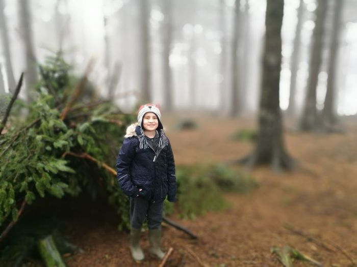 Tilt-shift portrait of smiling girl standing at forest during foggy weather
