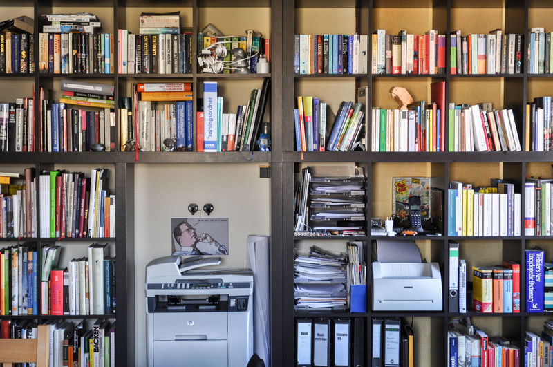 Books arranged in bookshelf at library