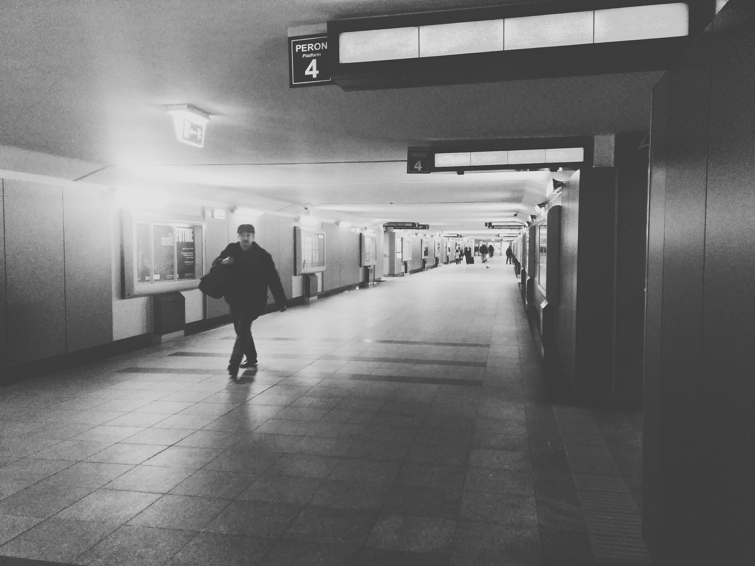 indoors, full length, men, illuminated, walking, lifestyles, rear view, corridor, architecture, built structure, the way forward, person, subway, leisure activity, flooring, lighting equipment, casual clothing, wall - building feature