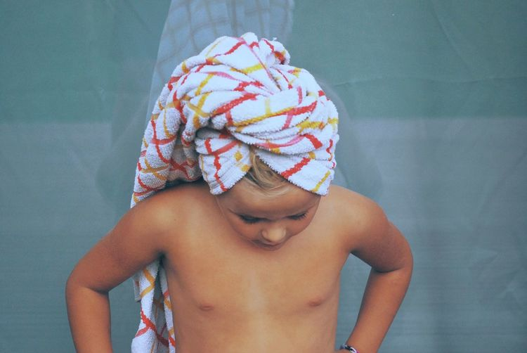 High angle view of shirtless girl wearing towel standing against wall