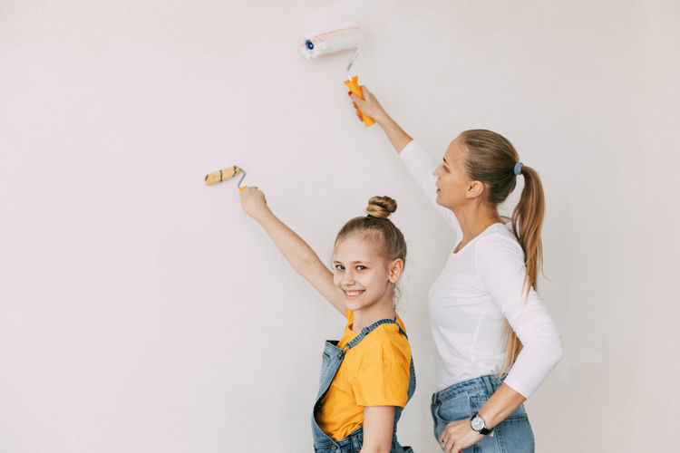 Beautiful and happy mom and daughter paint the walls in the apartment white.