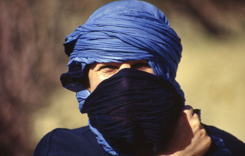 Close-up portrait of man covering face outdoors