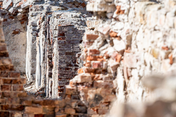 Close-up of a fragment of the ruins of an old stone building on a sunny day, selective focus