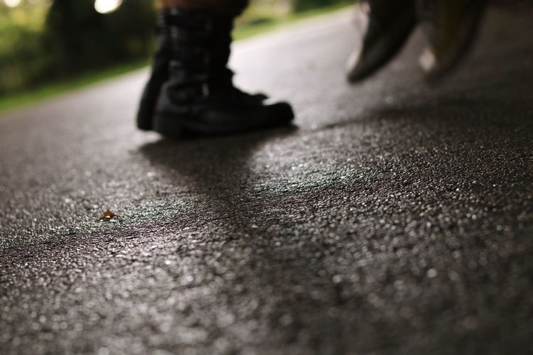 Low section of person walking on road