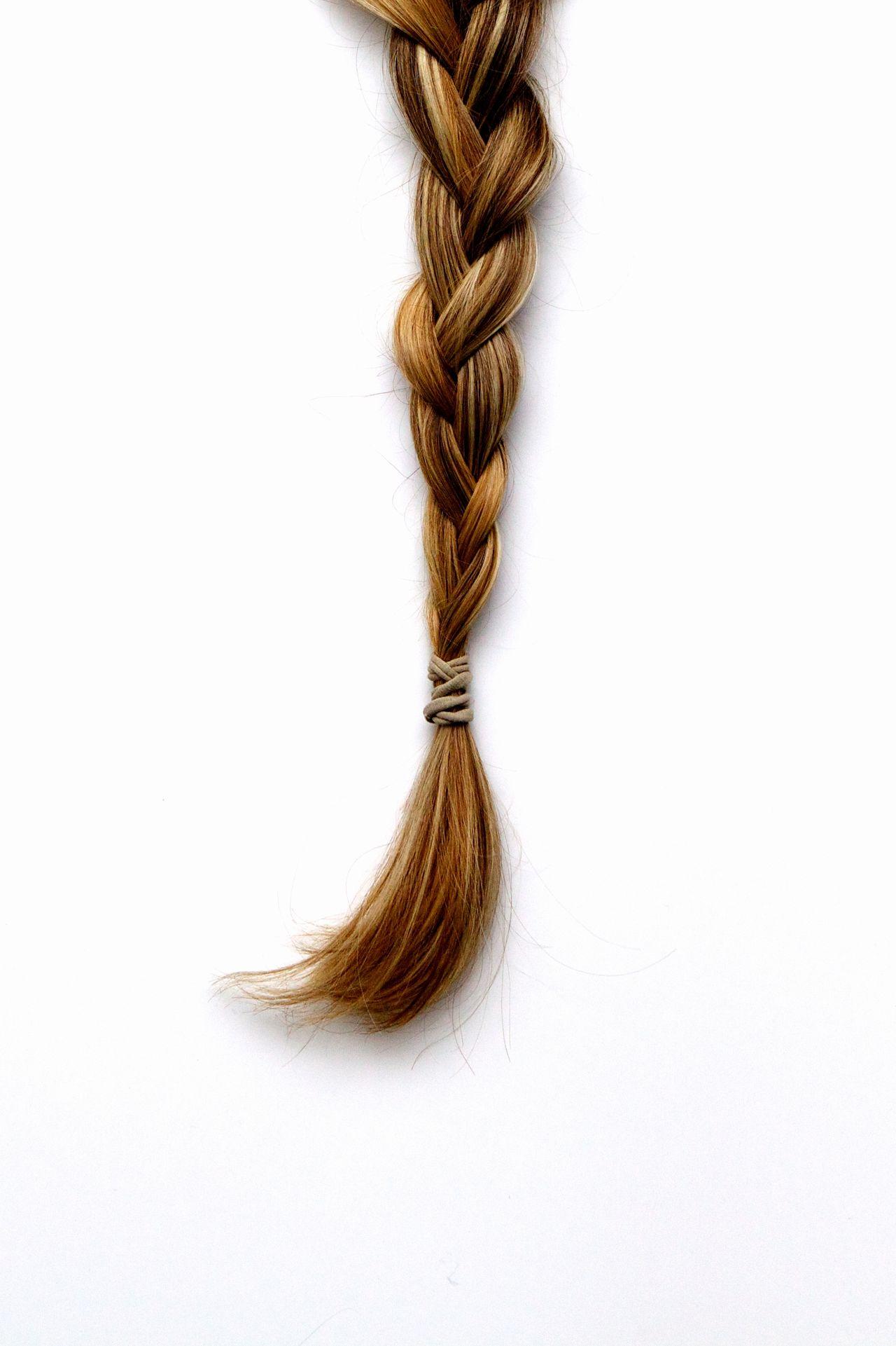 Blond braided hair against white background