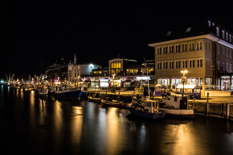 Boats Moored At Harbor Against Houses At Night