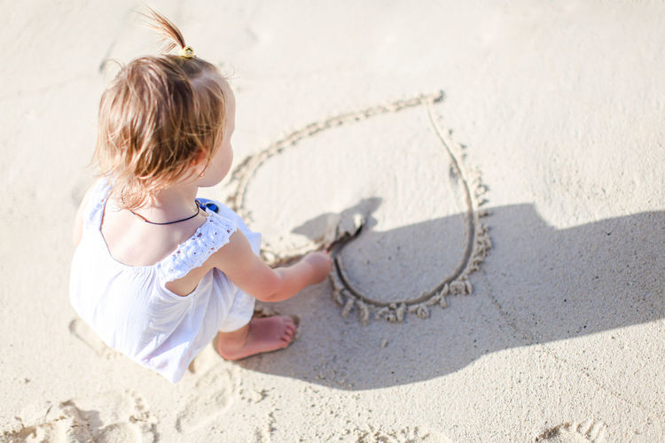 High angle view of girl on sand at beach
