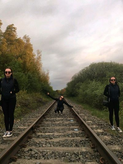 Man walking on railroad track against sky