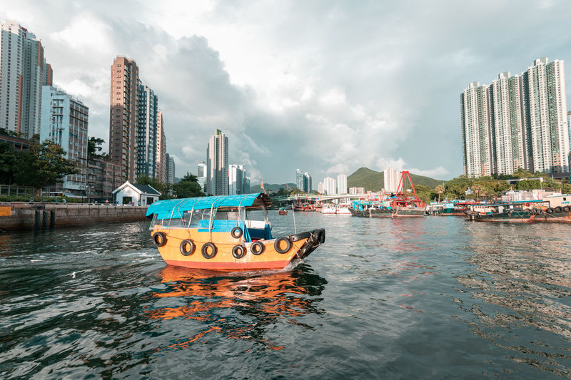 Boats moored in sea against buildings in city