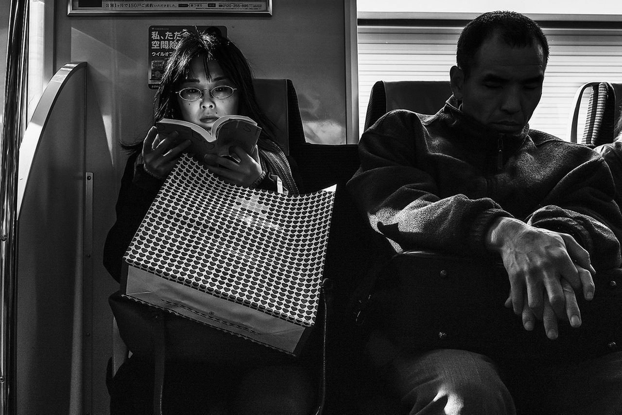 PORTRAIT OF FRIENDS SITTING ON SEAT IN ROOM