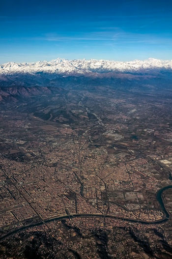 "The city under the Alps An aerial view of the Italian city of Torino (Turin) and the Italian Alps as a backdrop on a very clear day. Torino is the regional capital of Piemonte (Piedmont), literally ""at the feet of the mountain(s)"" and I think this image shows why Scenics - Nature Beauty In Nature Environment Sky Landscape No People Day Mountain Aerial View Land High Angle View Physical Geography Dramatic Landscape Torino Turin Piemonte Piedmont Italy Piedmont City Cityscape Urban From The Air River Po River Alps Italian Alps Alps Italy Mountain Range Snow Capped Mountains Valley Space For Text Urban Planning Clear Day Detailed"